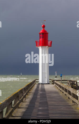 The red painted East lighthouse protecting the harbour at Trouville-sur-Mer, Normandy, France with a storm coming in behind - Stock Photo