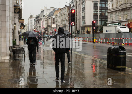 London, UK. 9th August, 2018. Typical English summer returns to the Strand in central London. The record breaking hot spell gave way to more typically English weather as heavy rain poured onto The Strand in central London. Umbrellas and light summer footwear made incongruous partnerships as buses, cars, taxis, cyclists and pedestrians all braved the downpour as they went about their business. © Peter Hogan/Alamy Live News - Stock Photo