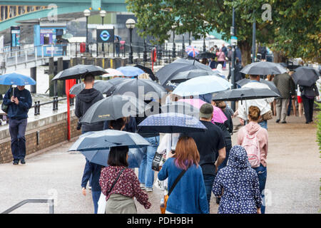 Bankside, London, UK. 9th August, 2018. Londoners get out their umbrellas and raincoats as rain and cooler weather replace the recent heatwave. Michael Heath/Alamy Live News - Stock Photo