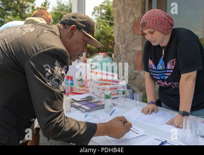 Massapequa, New York, USA. 5th Aug, 2018. Supporter writes his contact info on Volunteer Sign-In sheet, while campaign volunteer looks on, during opening of joint campaign office for Liuba Grechen Shirley, Congressional candidate for NY 2nd District, and NY Senator John Brooks, who are aiming for a Democratic Blue Wave in November midterm elections. Credit: Ann Parry/ZUMA Wire/Alamy Live News - Stock Photo