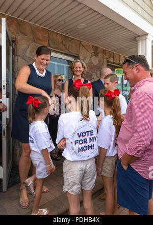 Massapequa, New York, USA. 5th Aug, 2018. Massapequa, New York, USA. August 5, 2018. L-R, JOANNE CURRAN PERRUCCI, candidate for Court Judge 4th District; and LAURA CURRAN, Nasssau County Executive, are smiling with Perrucci's four children, at opening of fellow Democrats' campaign office, aiming for a Democratic Blue Wave in November midterm elections. Credit: Ann Parry/ZUMA Wire/Alamy Live News - Stock Photo