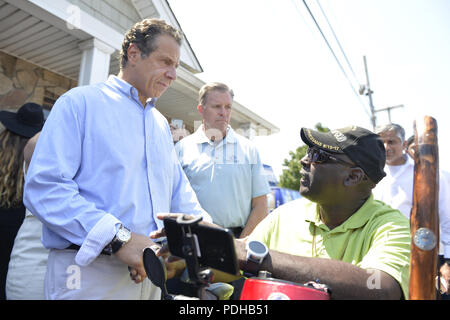 Massapequa, New York, USA. 5th Aug, 2018. Gov. ANDREW CUOMO, running for re-election, speaks with disabled man asking for government action helping the handicapped. The governor was a special guest at opening of joint campaign office for Grechen Shirley and NY Sen. J. Brooks, aiming for a Democratic Blue Wave in November midterm elections. Credit: Ann Parry/ZUMA Wire/Alamy Live News - Stock Photo