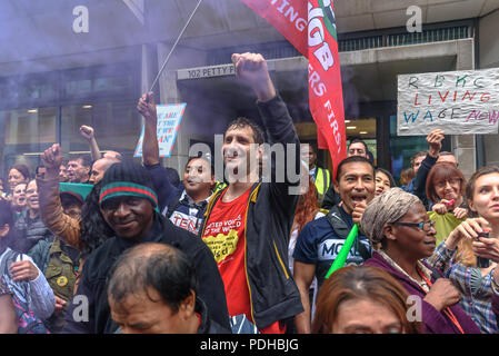London, UK. 9th August 2018. United Voices of the World cleaners and supporters celebrate the end of their 3-day strike with a rally outside the Ministry of Justice in Petty France. The strike was part of a coordinated action against the MoJ, Kensington & Chelsea council and hospitals and outpatient clinics in London run by Health Care America, demanding the London living wage and better conditions of employment. Credit: Peter Marshall/Alamy Live News - Stock Photo