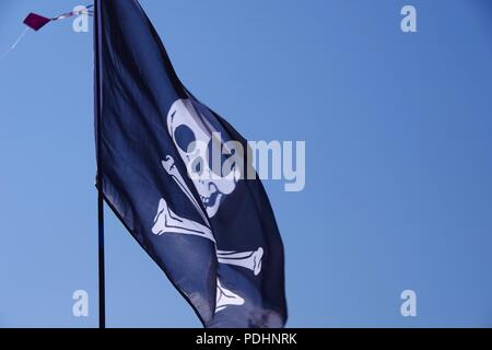 Jolly Roger Pirate Flag Flying against a Blue Sky. Sidmouth Folk Festival, East Devon, UK. August, 2018. - Stock Photo