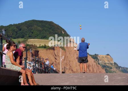 Juggler on the Promenade with Salcome Hill in the background. Sidmouth Folk Festival, East Devon, UK. August, 2018. - Stock Photo