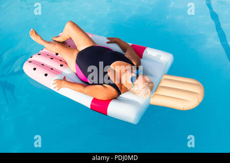 A senior female woman with bright sun glasses lies on a swimming pool inflatable icecream shaped float enjoying the sun - Stock Photo