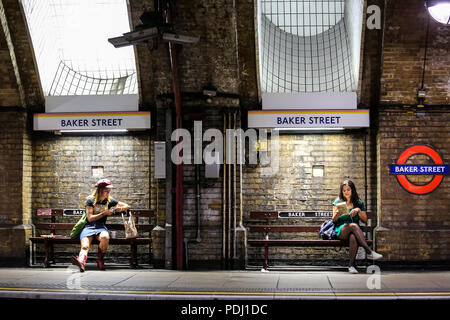 London, United Kingdom - 08-08-2018: two girls sitting and waiting for their train at Baker Street Tube station - Stock Photo