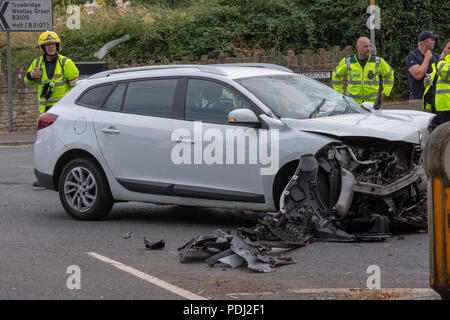Smashed up renault estate car with emergency service personnel in the background after a head on collision - Stock Photo