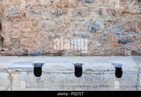 Stone communal toilets at Ephesus, an ancient Greek city settlement archaeological site on the Ionian coast near Selçuk, Izmir Province, Turkey - Stock Photo