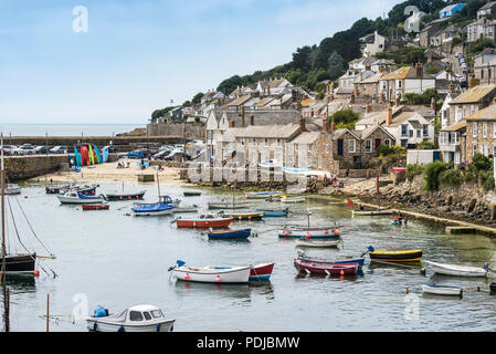 Small boats moored in the quaint harbour in Mousehole in Cornwall. - Stock Photo