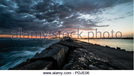 Stormy skys building over the Newcastle brake wall - Australia - Stock Photo