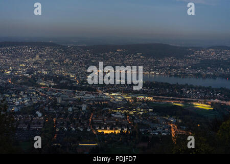 zurich city panorama at night sunset seen from uetliberg mountain - Stock Photo