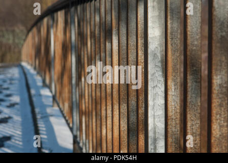 Metal, rusty bridge railing covered in snow lit by morning sun - Stock Photo