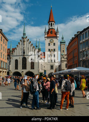 Munich, Germany - July 29, 2018: Tourists enjoy a sunny summer afternoon in front of the old Town Hall at Marienplatz Square in Munich - Stock Photo