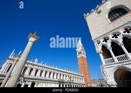 San Marco bell tower, National Marciana library and Doge palace low angle view, clear blue sky in Venice, Italy - Stock Photo