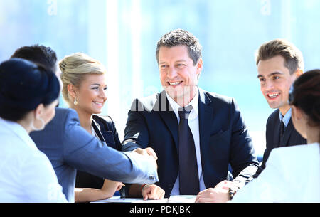 two business partners shaking hands on meeting - Stock Photo