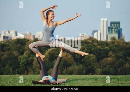 Two young beautiful Caucasian women yogi doing ninja acro yoga pose. Women doing stretching workout in park outdoors at sunset. Healthy lifestyle mode - Stock Photo