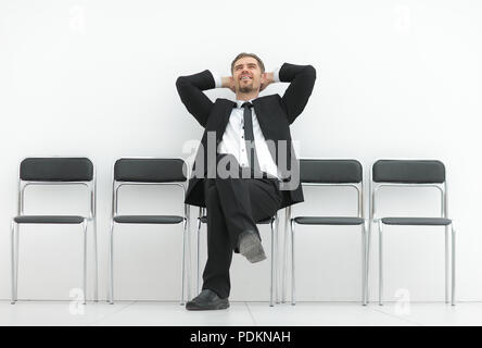 dreaming of a businessman sitting in an office corridor - Stock Photo