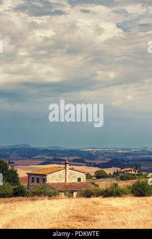 Rustic old house in the hills of Tuscany with sloping hay. Italy - Stock Photo