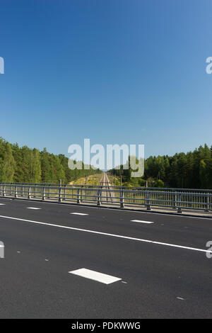 Latvia. Line highway with white markings on the bridge over the railway through a green forest and blue sky - Stock Photo