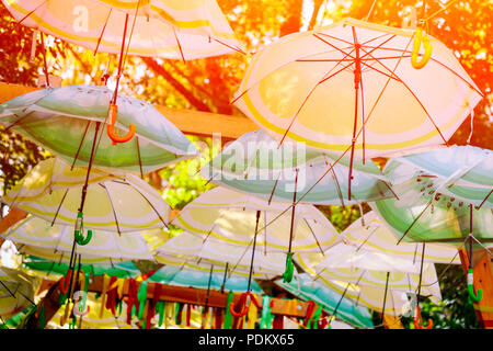 Concept shot of umbrellas of different colors in the air in park.  Many of the larger size hanging umbrellas. - Stock Photo