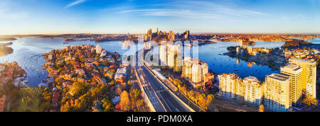 Wide aerial panorama of Sydney city CBD landmark around Harbour viewed from North Sydney along Warringah freeway lit by warm morning light. - Stock Photo