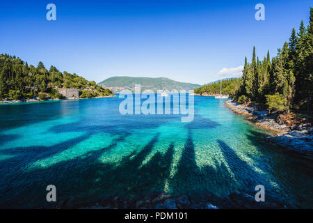 Beautiful Phoki Beach surrounded by cypress trees in the evening sunlight. Amazing seascape of Ionian Sea. Cypress shadows on the clear azure water. Greece - Stock Photo