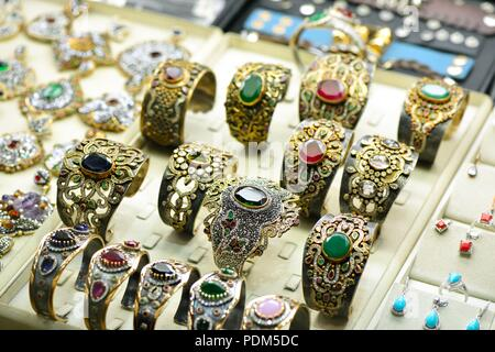 Golden colorful jewelry with gems in show room - Stock Photo