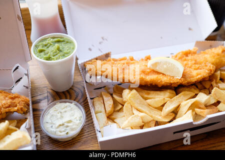 Fish and Chips takeaway with mushy peas and tartar sauce from Longsands Fish Kitchen in Tynemouth Village, Tyne & Wear, England. - Stock Photo