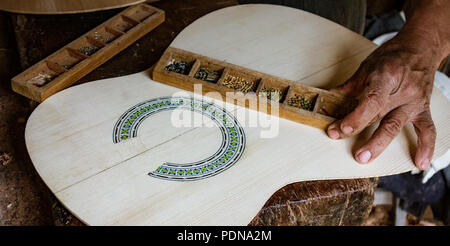 Man puts finishing touches on the inlay around a soundhole in a new instrument - Stock Photo