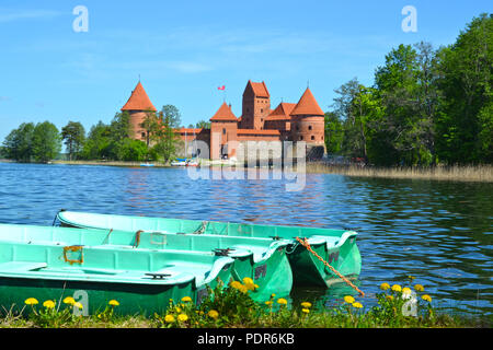 Three boats in the lake in front of Trakai Castle - Stock Photo