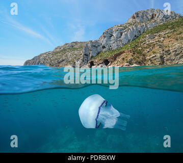 Rocky coast with a jellyfish and small fish underwater, split view above and below water surface, Mediterranean sea, Javea, Costa Blanca, Spain - Stock Photo