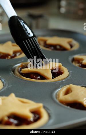 Brushing egg wash onto mince pies in a baking tray preparing them to be cooked in the oven - Stock Photo
