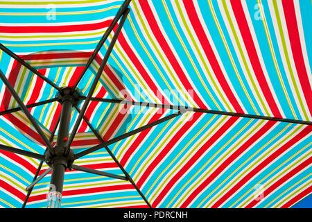 Colourful striped beach umbrella.  Closeup of colorful striped pattern on patio umbrella. - Stock Photo