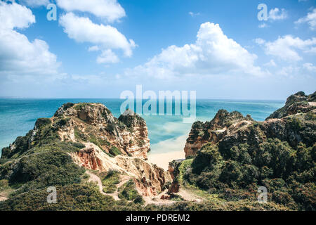 Beautiful views of the Atlantic Ocean and the rocks off the coast of Portugal next to the city called Lagos. From above the blue sky and clouds on a s - Stock Photo