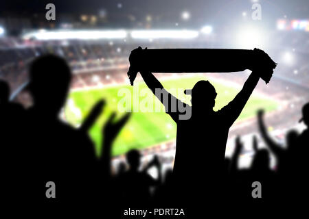 Crowd and fans in football stadium. People in soccer game. Person celebrating goal and holding merchandise scarf for favourite club and team in match. - Stock Photo