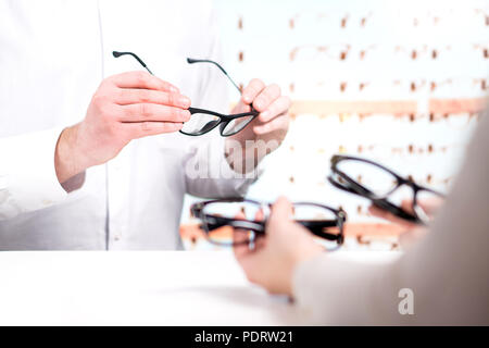Optician and customer choosing new glasses and trying different models. Eye doctor with client comparing spectacles and lenses in store. - Stock Photo