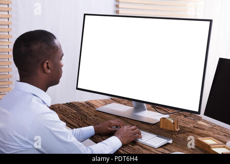 Close-up Of A Businessman Using Computer With Blank White Screen On The Wooden Desk - Stock Photo