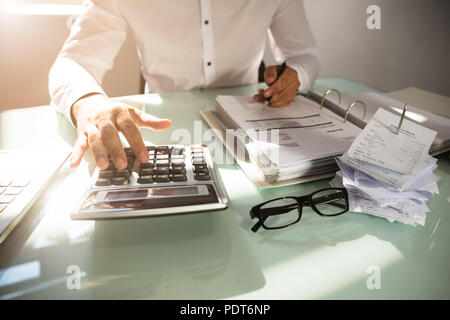 Close-up of a businessman's hand calculating bill in office - Stock Photo