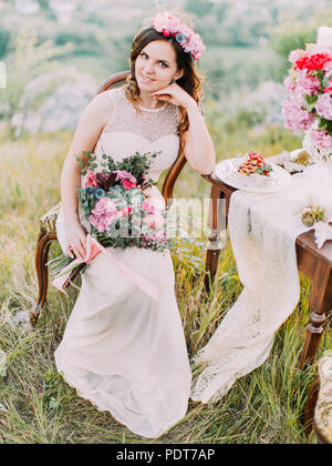 Close-up vertical view of the smiling bride with the wedding bouquet sitting near the table set. - Stock Photo