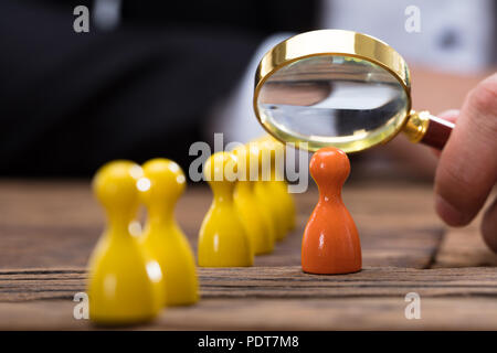 Businessperson's hand holding magnifying glass over orange pawn on wooden desk - Stock Photo