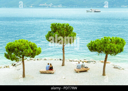 Two couples of different ages sitting on the beach of Limone sul Garda, Italy. - Stock Photo