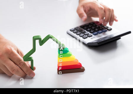 Close-up of a businessman using calculator holding outline of house model with energy efficiency rate - Stock Photo