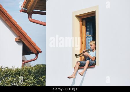 Little boy playing the trumpet in open window of the house. - Stock Photo