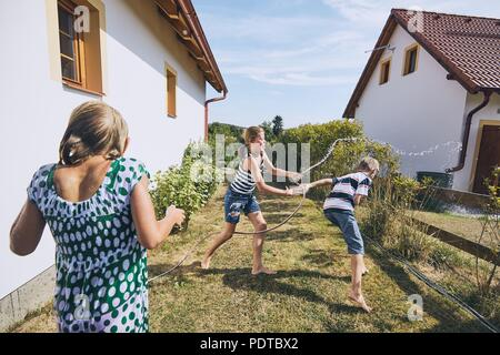 Children having fun with splashing water. Siblings on the back yard of the house during summer day. - Stock Photo
