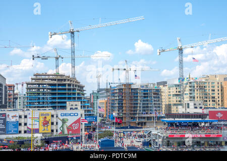 Seen from Nationals Park, construction cranes dominate new buildings in the rapidly developing Navy Yard neighborhood in Washington DC. - Stock Photo