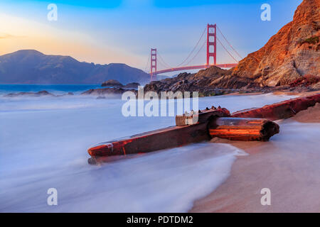 Famous Golden Gate Bridge view from Baker Beach at sunset in San Francisco, California - Stock Photo