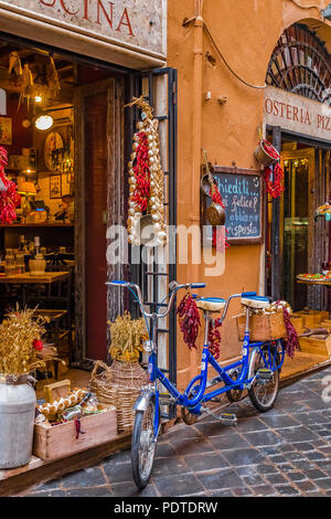 Rome, Italy - October 13, 2016: Old tahdem bike decorated with bunches of peppers and garlic in front of an osteria restaurant on a medieval cobblesto - Stock Photo