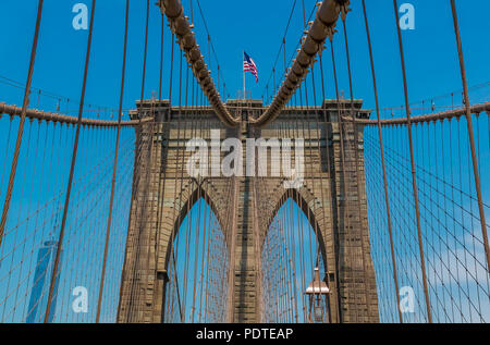 Close up view of the Brooklyn Bridge in New York, NY, one of the oldest suspension bridges in the United States with people on the bridge - Stock Photo