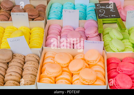 Colorful soaps shaped as macarons in boxes as exotic gift ideas for sale at a market stall in Southern France in Nice - Stock Photo